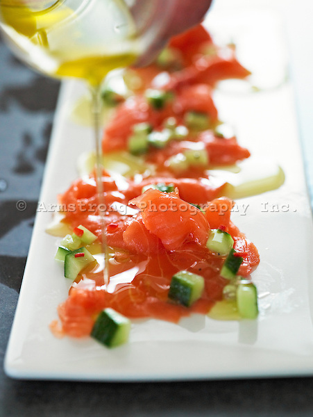 Salmon lox on a long plate with diced cucumber and olive oil