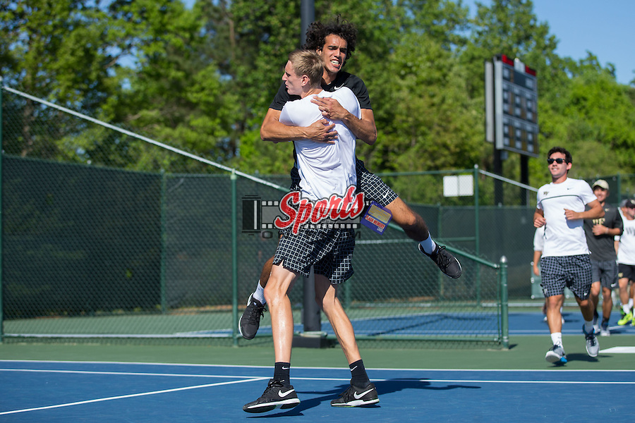 Skander Mansouri of the Wake Forest Demon Deacons jumps into the arms of teammate Christian Seraphim after Seraphim's three-set win at #5 singles in the 2016 ACC Men's Tennis Championship against the Virginia Cavaliers at the Cary Tennis Park on April 24, 2016 in Cary, North Carolina.  The Demon Deacons defeated the Cavaliers 4-3 to win their first ACC Men's Tennis Championship.  (Brian Westerholt/Sports On Film)