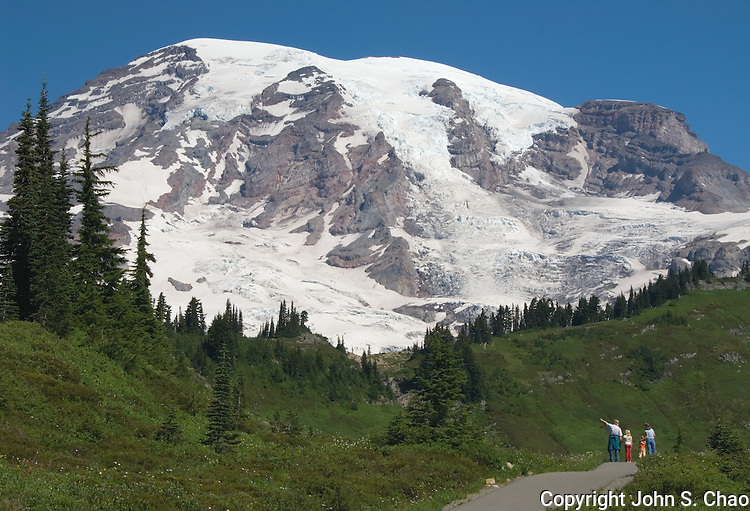 A family visiting the Paradise area of Mount Rainier National Park pause along a skyline pathway to marvel at The Mountain. Mount Rainier National Park, Washington State.....Photographed on digital media.