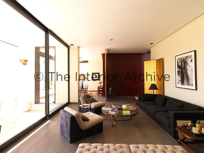 The large glass sliding doors in the living room open out onto the terrace and afford a view over the garden