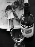 An opened bottle of red wine with empty wine glass in foreground, plate with eaten t-bone steak, fork, knife in background. Black and white image.