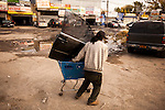 QUEENS, NY -- OCTOBER 22, 2013:   A man carries a BMW door with the help of a shopping cart in Willets Point on October 22, 2013 in Queens.  Photographer: Michael Nagle for The New York Times