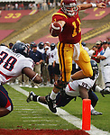 USC's Matt Leinart attempts to get the ball in the endzone, but comes up short as Arizona defender #38 Akin Akinniyi forces him to go out of bounds before crossing the endzone on Saturday, October 8, 2005 at the Los Angeles Memorial Coliseum. USC defeated the Azcats 42-21. Arizona's #93 Rickey Parker looks on.