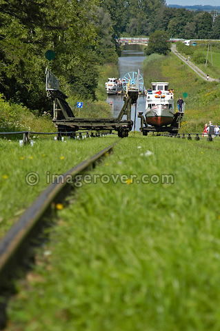 Boat on cable car being pulled uphill while empty cradle going downhill. Ostroda - Elblag Canal: Overland transportation of boats on rail cars at the Elblag Canal (Polish: Kanal Elblaskie, German: Oberlaendischer Kanal), Masuria, Poland, Europe. No releases available. ---Info: A system of rail-mounted cable trolleys on skipways and traditional locks are connecting the various sections of the Elblag Canal. A 100 metre difference in water levels is overcome during a length of 80 km between Ostroda and Elblag. The rail lift devices are mechanically driven by water power.--- HISTORY: The canal was designed in 1825-1844 by Georg Steenke, carrying out the commission given by the king of Prussia. Construction began in 1844. As the route was not important enough to justify building expensive, traditional locks between lakes, an ingenious system of tracks was employed instead, though the canal includes a few locks as well. Built originally under the name Oberländischer Kanal (Overland Canal) and situated in the Kingdom of Prussia, it was opened in 1860. Since 1945 the canal has been located in Poland. After wartime damage was repaired, it was restored to operation in 1948. Today it is used mainly for recreational purposes. It is considered one of the most significant monuments related to the history of technology on the territory of modern Poland..