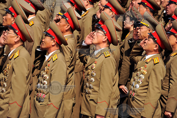Soldiers, parading in Kim Il-sung Square, salute during a ceremony marking the 100th birthday of Kim Il-sung.