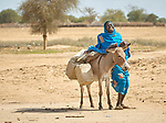 A young woman and her donkey in a camp for families displaced in the Darfur region of Sudan by fighting between government forces, Arab militias, and rebel soldiers.