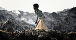 A boy scavenges in the smoldering municipal garbage dump in Chennai, India. He and other boys who work in the dump spend their nights safely in a shelter sponsored by the Madras Christian Council of Social Service.