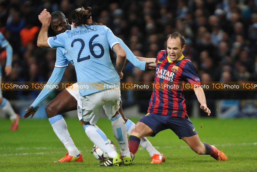 Andres Iniesta of Barcelona goes in for a challenge with Yaya Toure and Martin Demichelis of Manchester City - Manchester City vs Barcelona - UEFA Champions League First Knockout Round at the Etihad Stadium, Manchester - 18/02/14 - MANDATORY CREDIT: Greig Bertram/TGSPHOTO - Self billing applies where appropriate - 0845 094 6026 - contact@tgsphoto.co.uk - NO UNPAID USE