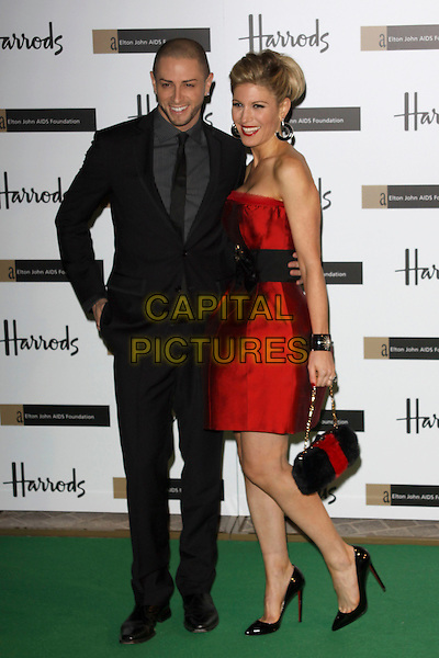 BRIAN FRIEDMAN & HOFIT GOLAN.The Emerald Ball in aid of The Elton John AIDS Foundation, Harrods, London, England. .November 5th, 2009.full length black suit blue red strapless silk satin dress leg up bag purse .CAP/AH.©Adam Houghton/Capital Pictures.
