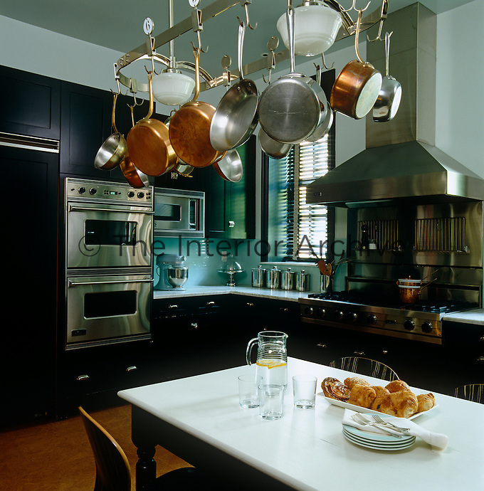 A collection of copper pots and pans hangs from a practical rack above the large table in the middle of the functional kitchen