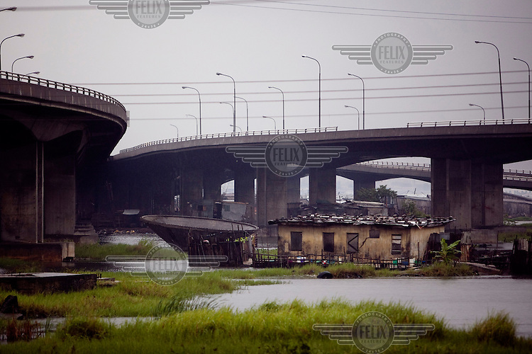 A house stands between flyovers. The country's infrastructure construction is funded by oil revenues. During boom times elaborate bridges and highway systems are built, and then left to crumble and collapse without repairs until the next oil revenue bubble.