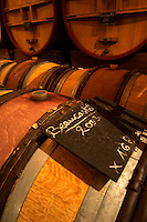 The aging cellar with oak barrels and larger wooden vats. Sign on chalk board saying Beaucastel 2003. Chateau de Beaucastel, Domaines Perrin, Courthézon Courthezon Vaucluse France Europe