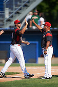 Batavia Muckdogs pitcher Joel Effertz (56) high fives hitting coach Luis Quinones (19) after the first game of a doubleheader against the Auburn Doubledays on September 4, 2016 at Dwyer Stadium in Batavia, New York.  Batavia defeated Auburn 1-0 in a continuation of a game started on August 13. (Mike Janes/Four Seam Images)