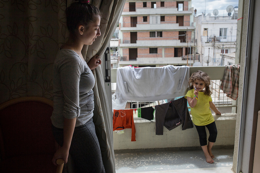 Evin Hassan, 15, left, a refugee from Afrin, Syria with her cousin, Fidan Daoud, on the balcony of their room at City Plaza Hotel in Athens, a refugee squat established by a pro-refugee solidarity group. The residents are currently under threat of eviction, following a court order.