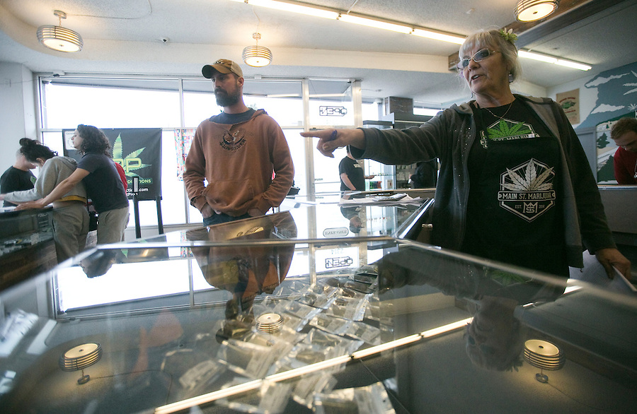 Budtender Cher Poff helps a customer at Main Street Marijuana in downtown Vancouver February 14, 2017. (Photo by Natalie Behring for the Columbian)