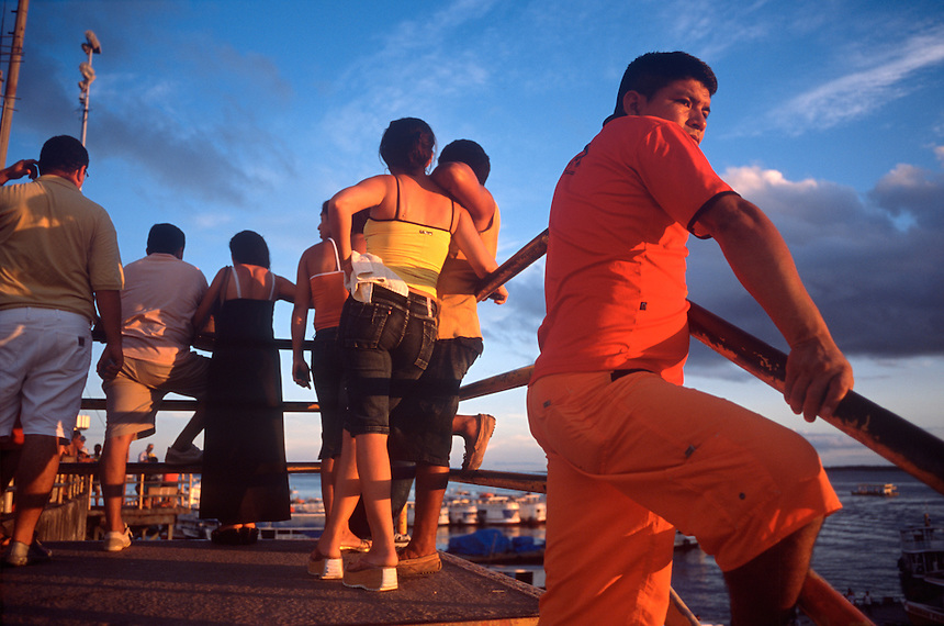 Residents watch the sunset along the beach port of the Rio Negro in Manaus, Brazil, Monday, Jan. 9, 2006. With few roads leading to the outside world, most goods are brought to the city 1,000 miles inland from the coast by boat. (Kevin Moloney for the New York Times)