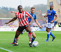 Lincoln City's John Akinde shields the ball from Macclesfield Town's Fiacre Kelleher<br /> <br /> Photographer Chris Vaughan/CameraSport<br /> <br /> The EFL Sky Bet League Two - Lincoln City v Macclesfield Town - Saturday 30th March 2019 - Sincil Bank - Lincoln<br /> <br /> World Copyright © 2019 CameraSport. All rights reserved. 43 Linden Ave. Countesthorpe. Leicester. England. LE8 5PG - Tel: +44 (0) 116 277 4147 - admin@camerasport.com - www.camerasport.com