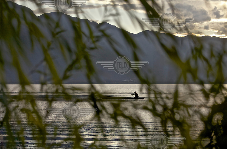 A fisherman paddles his boat on Lugu Hu Lake. /Felix Features