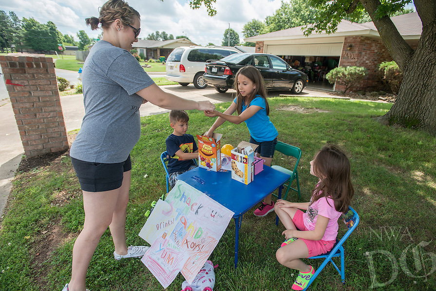 NWA Democrat-Gazette/ANTHONY REYES &bull; @NWATONYR<br /> Faleesha Wooten (CQUED) buys snacks from Emily Dale, 9, (center) Raiden Dale, 7, (left) and Kaylen Dale 7, outside their home Monday June 13, 2016 in Springdale. The trio were selling granola bars, gummy fruit snacks and puppets to passing motorists on their neighborhood street. Raiden hope to buy trading cards with his share of the money.