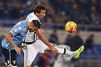 Calcio, Serie A: Lazio vs Juventus. Roma, stadio Olimpico, 4 dicembre 2015.<br /> Lazio&rsquo;s Mauricio, left, and Juventus&rsquo; Mario Mandzukic jump for the ball during the Italian Serie A football match between Lazio and Juventus at Rome's Olympic stadium, 4 December 2015.<br /> UPDATE IMAGES PRESS/Riccardo De Luca