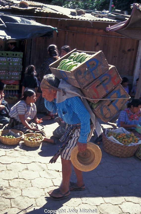 Elderly Maya man carrying a heavy load using a traditional trump line around his forehead, Sunday market in Chichicastenango, Guatemala