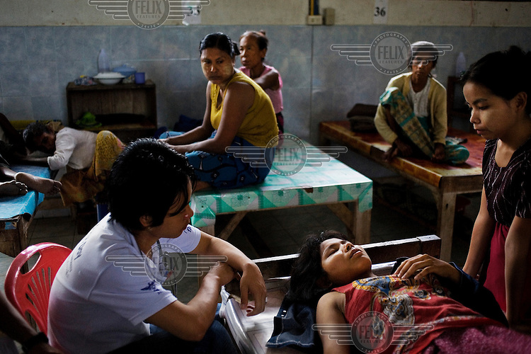 A patient with severe malaria lies on a table in Mae Tao clinic, Mae Sot.