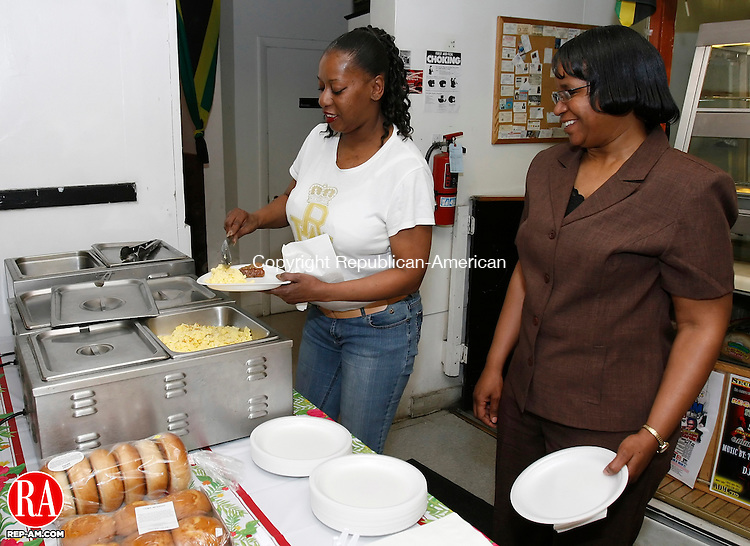 WATERBURY, CT, 05/10/09- 051009BZ01- Katrina Bell, of Waterbury, left, mother of three and grandmother of three, and Cathy Gause, of Waterbury, mother of a daughter, enjoy a free Mother's Day breakfast buffet at Mikey's Jamaican Restaurant on East Main Street in Waterbury Sunday morning.  Restaurant owner Michael Anderson provided the free meal to every mother who came in to eat.<br /> Jamison C. Bazinet Republican-American