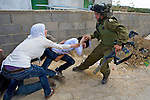 An Israeli soldier drags away a young Palestinian woman as she tries to protect an injured peace activist from the soldiers in the village of An Nabi Salih near Ramallah on 11/06/2010. The injured man had tried to prevent a fight between the soldiers & two Palestinian women & was knocked to the ground by a soldier who subsequently kicked him as he lay injured.