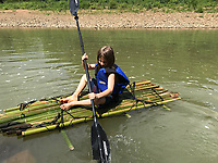 """READING INSPIRED RAFT<br />Clayton Niederman, 10, paddles a raft he and his brother, Edmond Niederman, 12, built with bamboo and empty plastic bottles they recycled into the raft's floatation. The boys got the idea for the project after reading """"The Raft,"""" a book about a child in Maine who paddled a raft, said their mom, Gina Niederman of Fayetteville. Brisk sales of kayaks made it difficult for the family to find kayaks to buy and that also helped spark the project.<br />(Courtesy photo)"""