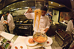 Cook dishes out a plate of spaghetti in a San Francisco restaurant