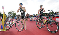 22 JUL 2007 - LONDON, UK - Richard Stannard puts on his helmet as Alistair Brownlee makes his way from transition - Corus Elite Triathlon Series. (PHOTO (C) NIGEL FARROW)