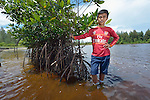 Jefrin Zendrato, 13, poses among mangroves he helped plant as a small boy in 2007 near his village of Moawo on the Indonesian island of Nias. The mangrove planting was part of assistance provided to the village by YEU, a member of the ACT Alliance, following a devastating 2004 tsunami and 2005 earthquake. Residents say the mangroves have helped to protect the shoreline from erosion and attracted crabs and small fish which have helped to revitalize their fishing industry. <br /> <br /> (Parental consent obtained.)