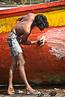 Chatham bay at the Andaman Islands, India. A boy is cleaning the hull of a local wooden boat before re-painting it