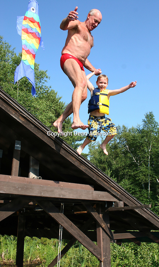 A man and his grandson jump off the roof of a boat house and into the lake.