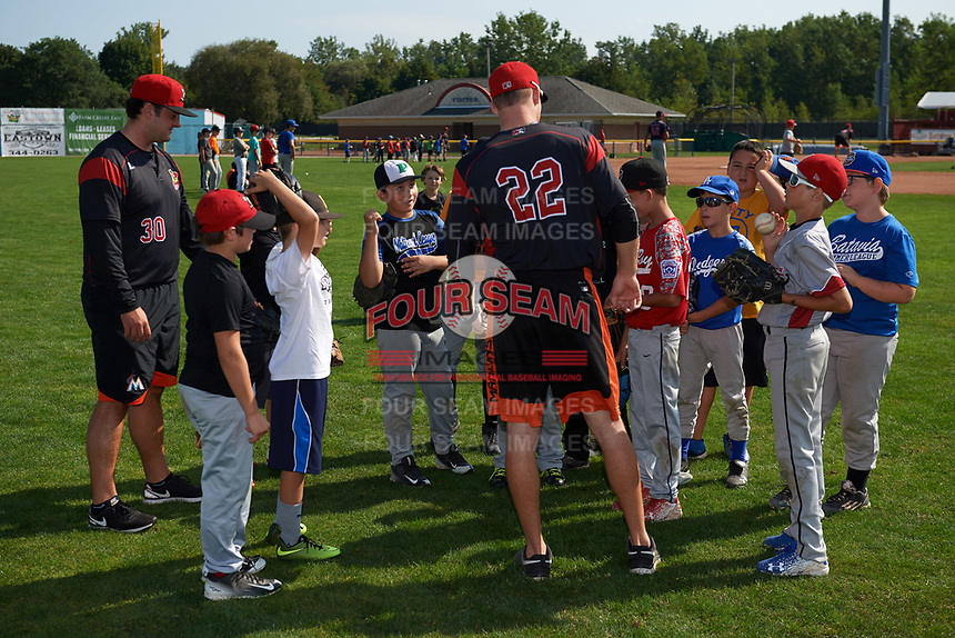 Batavia Muckdogs pitchers Bryce Howe (30) and Travis Neubeck (22) meet with participants during the teams youth baseball clinic on August 30, 2017 at Dwyer Stadium in Batavia, New York.  (Mike Janes/Four Seam Images)