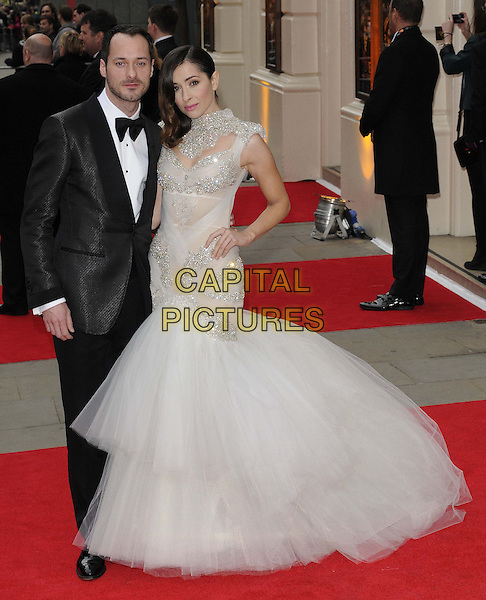 Declan Bennett & Zrinka Cvitesic.The Laurence Olivier Awards held at the Royal Opera House - Arrivals, London, England..April 28th, 013.full length black tuxedo grey gray silver layered tulle fishtail dress hand on hip.CAP/CAN.©Can Nguyen/Capital Pictures.