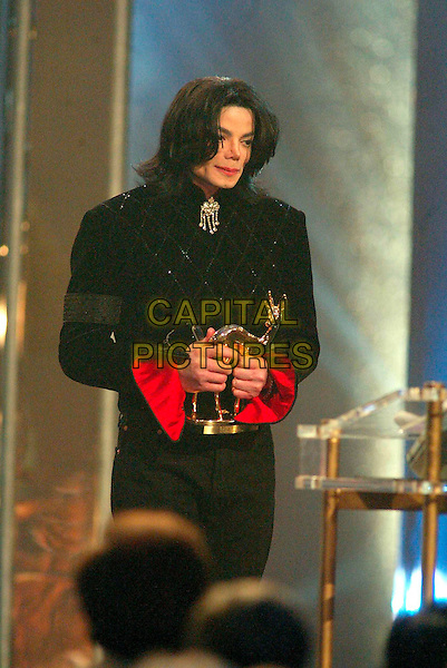 MICHAEL JACKSON.Michael Jackson dies at the age of 50 after suffering a heart attack on July 25th, 2009 .Bambi Awards, Estrel Hotel, Berlin, Germany..November 21st, 2002.half length black jacket award trophy red cuff sleeve .CAP/PPG/WS.© Willi Schneider/People Picture/Capital Pictures