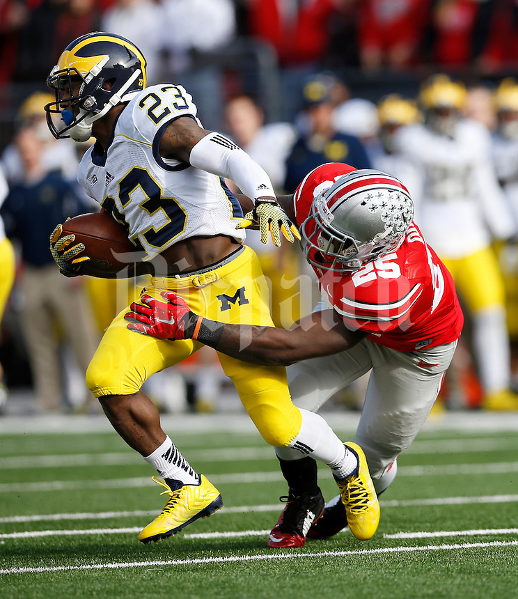 Ohio State Buckeyes running back Bri'onte Dunn (25) tackles Michigan Wolverines wide receiver Dennis Norfleet (23) on a kickoff during the first quarter of the NCAA football game at Ohio Stadium on Nov. 29, 2014. The Buckeyes won 42-28. (Adam Cairns / The Columbus Dispatch)