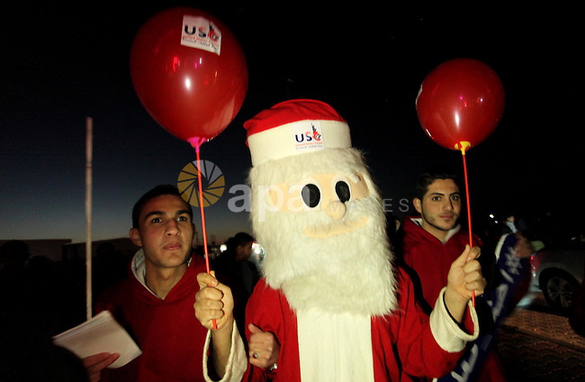 A Palestinian man in Santa Claus costume takes part in the celebration of the New Year at the Gaza seaport, on December 31, 2016. Photo by Ashraf Amra