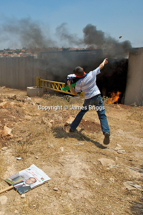 A Palestinian child throws stones at [unseen] Israeli soldiers on the other side of Israel's controversial separation barrier built on Palestinian land in the village of Ni'lin near Ramallah on 16/07/2010.