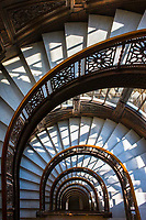 The wonderfully designed semi-circular staircase at the Rookery Building, a historic landmark located in the Loop community area of Chicago in Cook County, Illinois, United States. Completed by John Wellborn Root and Daniel Burnham of Burnham and Root in 1888, it is considered one of their masterpiece buildings. It once housed the office of the famous architects. It measures 181 feet (55 m), is twelve stories tall and is considered the oldest standing high-rise in Chicago. It has a unique style with exterior load-bearing walls and an interior steel frame. The lobby was remodeled in 1905 by Frank Lloyd Wright. Starting in 1989, the lobby was again restored to the original Wright design.<br /> The Rookery was built in 1887&ndash;1888 in the architectural boom that followed the Great Chicago Fire, architects in what would become known as the Chicago School of commercial architecture competed with each other to create the world's first true skyscrapers. By mixing modern building techniques, such as metal framing, fireproofing, elevators and plate glass, together with traditional ones, such as brick facades and elaborate ornamentation, Burnham and Root sought to create a bold architectural statement. At the same time, they intended their buildings to be commercially successful. This building is one of the few results of their partnership that is still standing.<br />  As the master artisan, Root drew upon a variety of influences in designing the interior and exterior spaces, including Moorish, Byzantine, Venetian and Romanesque motifs. He also provided the architectural innovations that brought together many contemporary cutting edge building techniques. Of particular note was a &quot;floating&quot; foundation&mdash;a reinforced concrete slab that provided the building's weight with a solid platform atop Chicago's notoriously swampy soil. The term for the type of foundation that Root designed is grillage foundation, a foundation where iron rails and the structural beams are combined in a crisscross p