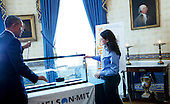 United States President Barack Obama looks at the generator of Corine Peifer and Kristian Sonsteby from Wallenpaupack, Pennsylvania that use the movement of a boat dock to produce electricity during the 2015 White House Science Fair, a celebration of students winners of STEM (Science, technology, engineering and math) competitions from across the country on March 23, 2015,  at the White House in Washington, DC. <br /> Credit: Aude Guerrucci / Pool via CNP