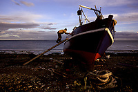 A fisherman in Punta Arenas, Chile, scrambles up a plank to finish a new coat of paint on his boat. Late evening light bathes the Strait of Magellan at 10:30 p.m. as the summer days grow long near the antarctic.