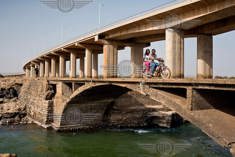 A couple cross an arch spanning a rivulet of the Niger River with the Chinese built bridge in the background. It was opened in September 2011 and is the third crossing of the Niger in Bamako.