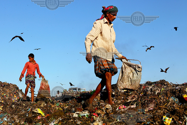 A man and a boy look for recyclable material at the biggest rubbish dump in Dhaka. The city alone generates about 3500 to 4000 metric tons of solid waste each day.