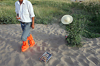 A vendor selling goods to tourists walking on sand dunes at the tourist attraction of Ming Sha Shan. Dunhuang, Gansu Province. China