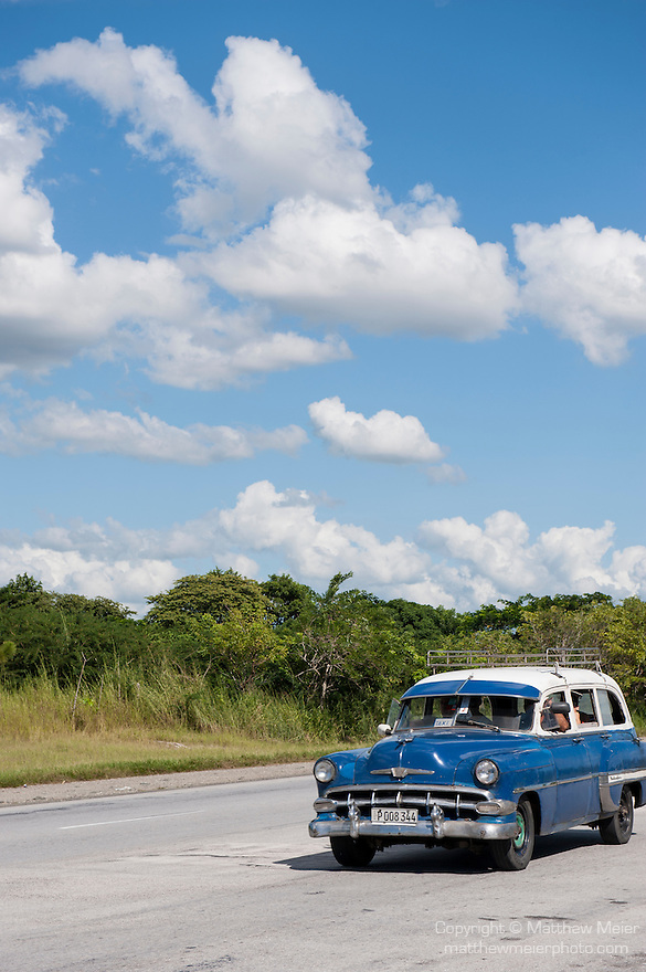 Cuba; a blue and white, classic 1953 Chevy station wagon driving along the highway from Havana to Jucaro