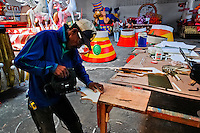 A Colombian man works in the Carnival workshop, Barranquilla, Colombia, 23 February 2006. The Carnival of Barranquilla is a unique festivity which takes place every year during February or March on the Caribbean coast of Colombia. The allegorical floats and masks are created by artists with their teams. These crews are highly specialized to design and create large floats because they keep this profession in the family for decades.