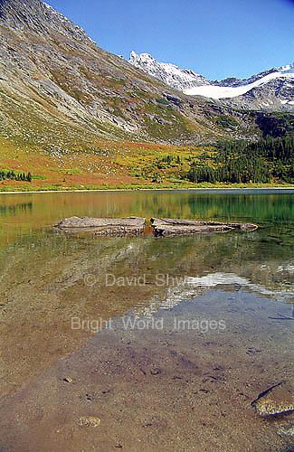 Upper Dewey Lake near Skagway, Alaska reflects the surrounding mountains, trees, and sky.