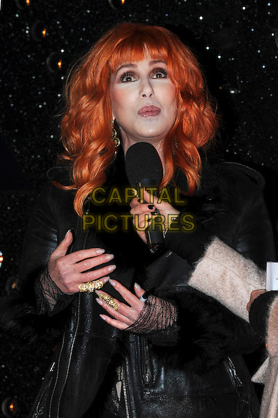 CHER  (Cherilyn Sarkisian) .'Burlesque' UK Gala premiere at the Empire Cinema, Leicester Square, London, England, UK,.13th December 2010..half length black dress  lace mesh sleeves leather biker jacket fur sheepskin collar shearling red orange hair wig microphone interview hands gold rings.CAP/IA.©Ian Allis/Capital Pictures.
